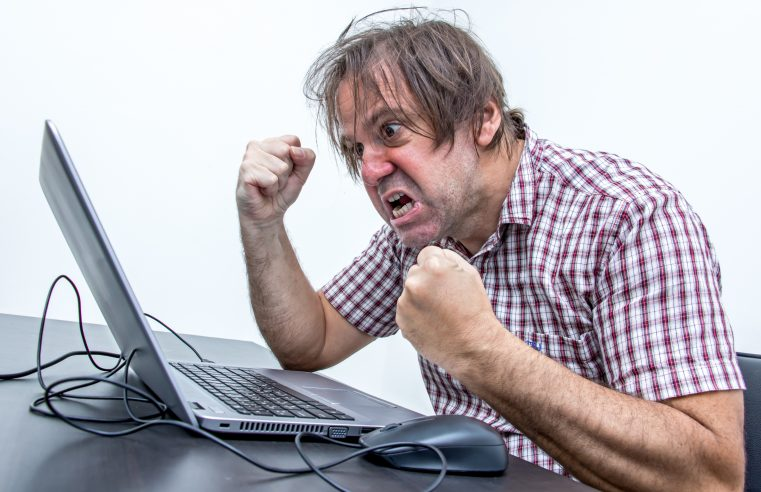 The angry user is screaming to the laptop. Aggressive man working with notebook at office. System error on computer.